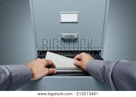 Office clerk searching for files in the filing cabinet data storage and archives concept personal point of view poster