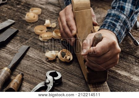 Carpenter working in his workshop he is smoothing a wooden board using a planer carpentry carpentry woodworking and craftsmanship concept poster