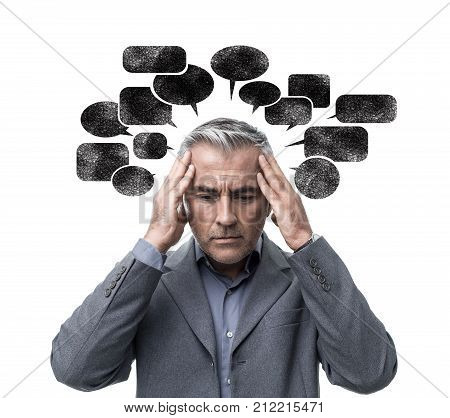 Pensive stressed man having negative thoughts and feeling confused he is surrounded by dark speech bubbles