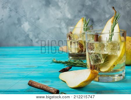 Pear cocktail with rum liquor pear slices and rosemary on an blue wooden table selective focus. Copyspace