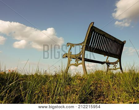 Bench on the dike with sky and clouds