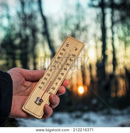 hand holding thermometer with sub-zero temperatures in the winter forest