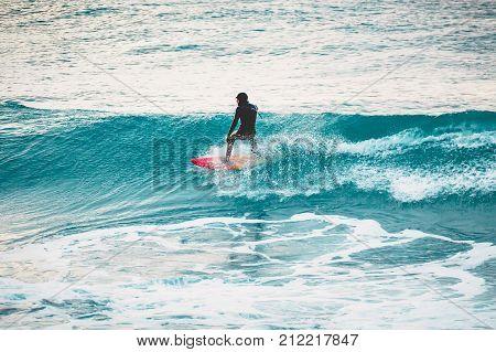 Winter surfing in ocean. Surfer on blue wave