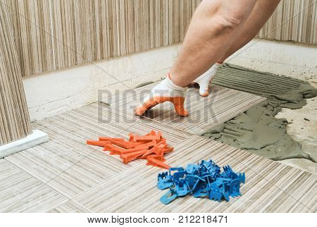 Installation of ceramic tiles. A tile's hand is puting a tile on an adhesive.