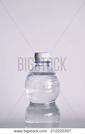 a transparent glass full of water. near a bottle of mineral water. composition with bottles of mineral water