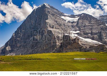Majestic north face of Eiger mountain (3.967m - 13.015ft) and train to Jungfraujoch in the Bernese Alps in summer. Kleine Scheidegg Bernese Oberland Switzerland.