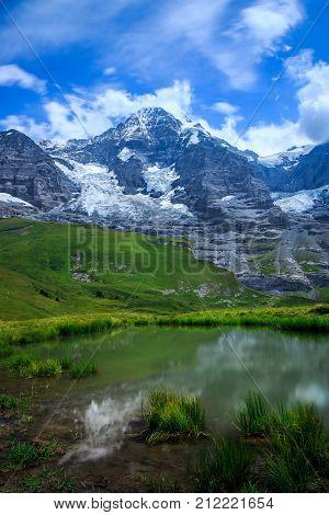 Mountain Monch (4.107m - 13.474ft) and Jungfraujoch + reflection in water in the Bernese Alps in Summer. Kleine Scheidegg Bernese Oberland Switzerland.