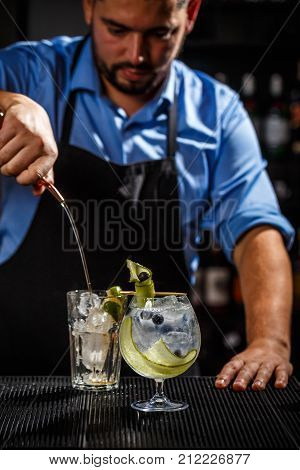 Bartender is preparing a gin tonic cocktail