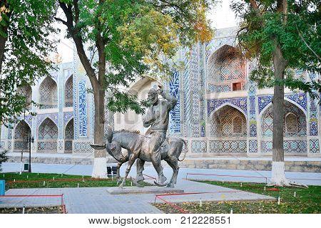 2013 November 11, Sculpture of Nasreddin Hodja against ancient mosque wall, Bukhara, Uzbekistan