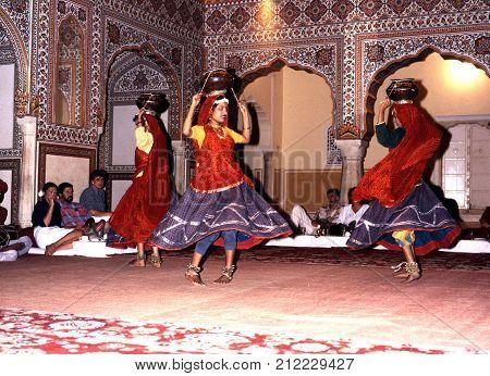 SAMODE, INDIA - NOVEMBER 22, 1993 - Indian dancers balancing pots on their heads performing at the Samode Palace with a musical band to the rear Samode Rajasthan India, November 22, 1993.
