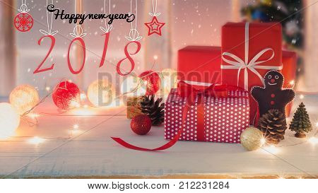 Christmas and New Year holidays gift box with decorative ornament on white wooden table with falling snow effect.New Year 2018 sign background.Gifts and congratulations concept.