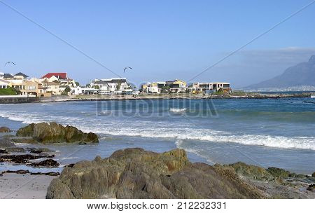 SUMMER SEASCAPE, WITH BOULDERS IN THE FORE GROUND AND HOUSES IN THE BACK GROUND AND A TRANQUIL TURQUOISE  SEA