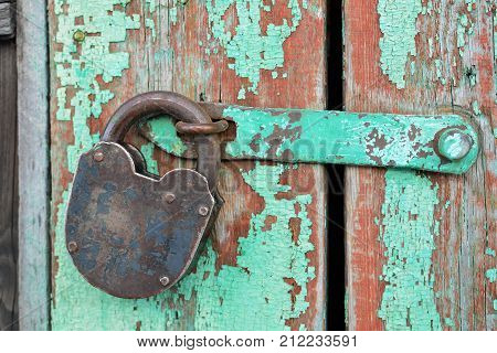 Old rusty padlock hanging on an old wooden door. Security concept: open padlock on wooden wall.
