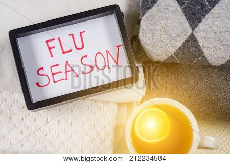 Protection from the flu season - warm woolen clothing and lot of hot drinks. Flu season - text in frame.