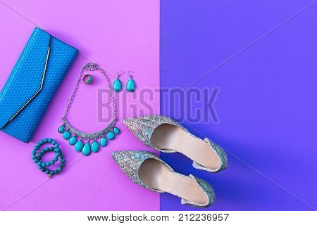 Fashion woman accessories set. Trendy fashion shoes heels stylish handbag clutch necklace bracelet and ring pink and purple background. Lifestyle Concept.