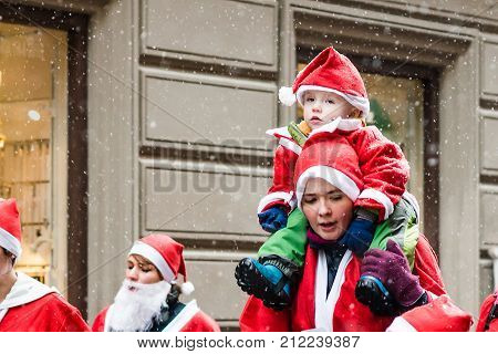 Stockholm, Sweden – December 11, 2016: Mother With A Small Child Dressed Up As Santas Participate In