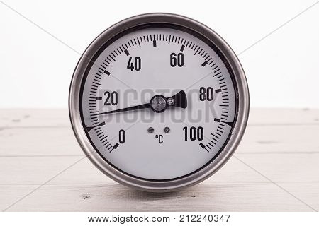 Dial Gauge Thermometer On A White Wooden Background