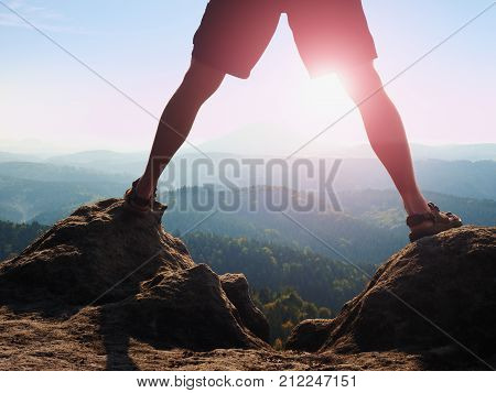 Hot Sun Between Naked Legs. Slim Legs  In Pants And Sandals Make Step On Rock  In Jungle