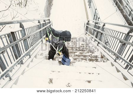 boy shoveling snow from the stairs. child cleans the stairway overpass after snowfall. view from above. the concept of selfless assistance, citizen responsibility