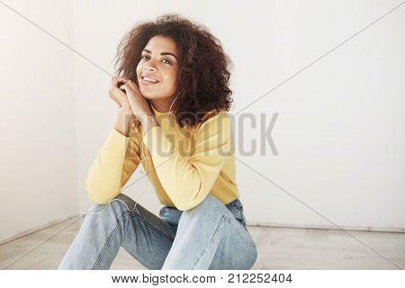 Close up of young good-looking joyful african girl with retro curly hairstyle in stylish yellow turtleneck and vintage jeans smiling with teeth, sitting on floor, looking in camera with happy and relaxed expression, listening to music with headphones