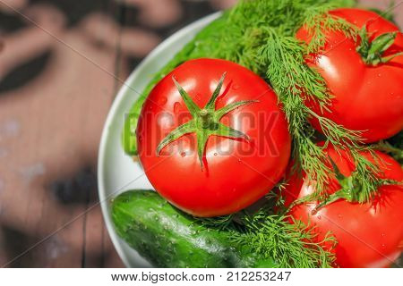 Fresh tomato and cucumbers on wooden table. Stock photo.
