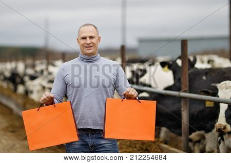 Farmer portrait against background of farm cows showing a product