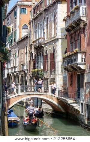 VENICE,ITALY- May 18, 2017 : Tourists on water street with Gondolas in Venice. its entirety is listed as a World Heritage Site, along with its lagoon