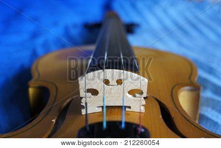 New violin bridge resting on the body of the instrument (closeup).