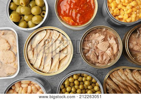 Open tin cans with different food on table