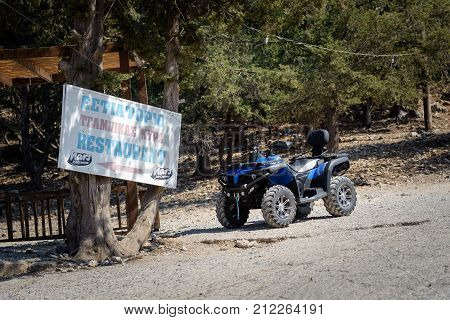 Rhodes, Greece - August 10, 2017: ATV motorbike is parked near entrance of traditional Greek tavern on Rhodes island.