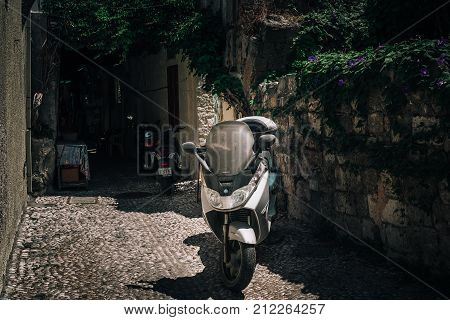 RHODES, GREECE - AUGUST 2017: Motorbike scooter is parked near the wall at narrow street of Rhodes town on Rhodes island, Greece