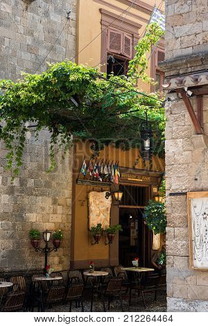 RHODES, GREECE - AUGUST 2017: Narrow street with small cafe in Rhodes town. Rhodes island, Greece