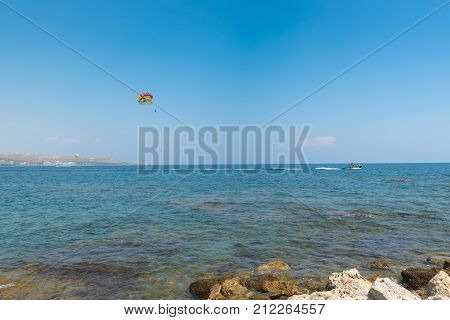 Flying paratrooper with full color parachute is flying over Rhodes island, Greece