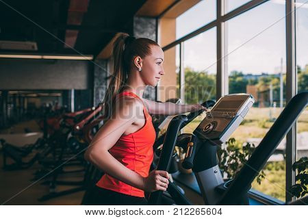 Sport girl run orbitrek gym body fitness concept. Hard cardio workout. All for the    of achieving the goal.