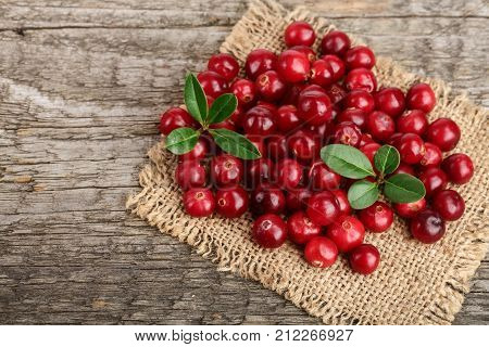 Cranberry with leaf on old wooden background.