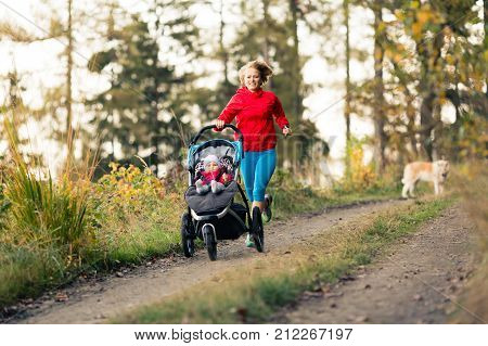 Running mother with child in stroller enjoying motherhood at autumn sunset and mountains landscape. Jogging or power walking woman with pram in woods. Beautiful inspirational mountains landscape.