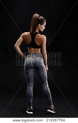 Shot of a strong woman with muscular abdomen in sportswear. Fitness female model posing on black background. A woman stands with her back and looks away