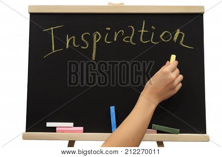 Inscription Inspiration written by yellow chalk on black board surface with copy space. New idea concept. Student girl holds a piece of chalk in her hand and writes it on the school board.