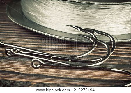Fishing hooks on old wooden table. Four hooks for fishing and a skein fishing line