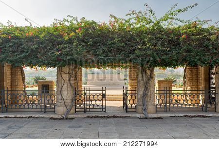 Cairo Egypt - December 7 2016: Entrance of Heliopolis Commonwealth War Cemetery with fence metal door climber green plants