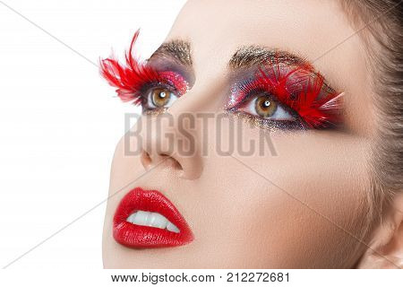 closeup fashion portrait of beautiful woman with vivid creative makeup isolated on white. Red lips. Makeup for party. False eyelashes feathers. Beauty, fashion, art make up concept