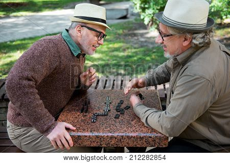 Enjoying retirement together. Cheerful senior male pensioners are playing dominoes while sitting at table in park. Man trying to look at hand of opponent with interest and smiling