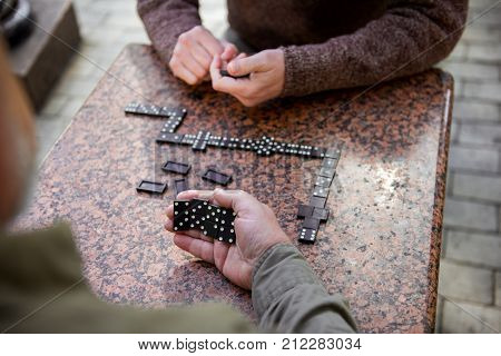 Close up top view of male hand holding dominoes while hiding it from opponent
