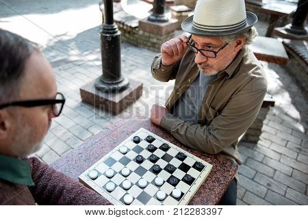 Are you sure with this move. Top view of serious mature man looking at his opponent in checker game with scrutiny. He is touching his eyeglasses while sitting at table