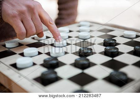 Close up of male hand moving white checker forward on chessboard