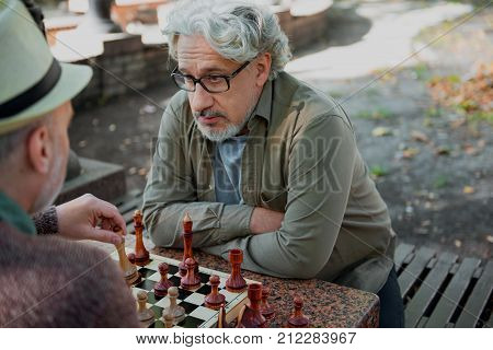 You will never win me. Portrait of confident mature man looking at his opponent with seriousness while one is moving figurine on chessboard. Competition concept