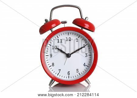 Red alarm clock isolated on white backgroundshows ten hours ten minutes of the morning time to get up to wake up and have breakfast morning or evening jog to go to work.