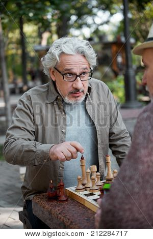 Your move. Portrait of serious mature man pointing finger at his opponent during chess game. They are sitting at table in park