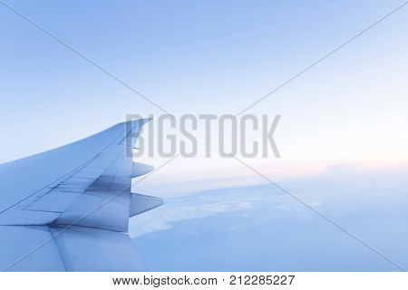 View from a passenger airliner window of an airplane wing clouds and sky