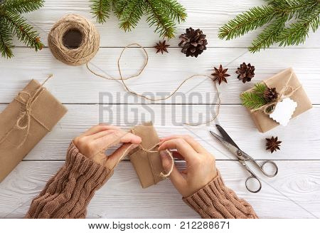 Preparation christmas gifts on a white wooden table with fir branches